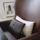 White and brown cushions on a brown leather armchair