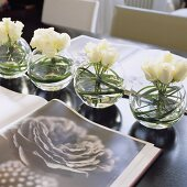 White roses in round glass vases and an open book with a picture of a flower