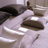 A symmetrical arrangement of cushions on a bed