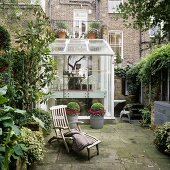 Two story greenhouse in front of a home with brick facade and old wooden deckchair in a backyard