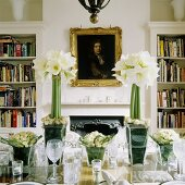A festively decoration table with white amaryllis in a glass vase and a picture over a fireplace