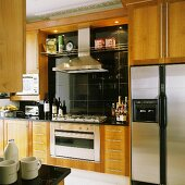 Wooden kitchen cupboards and a built-in cooker with an extractor fan against black wall tiles