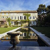 A house in Provence and antique Greek urns by a pool in the garden