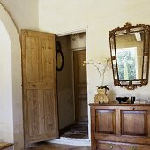 A living room with an open door and an antique sideboard with a mirror