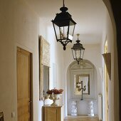 Foyer in a Provencal house with lanterns hanging from the ceiling and a view through rounded arches on an antique console table with a mirror