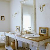 A simple washstand with two basins and a white framed, illuminated mirror in the bathroom of a country house