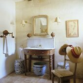 Ceramic jars under a simple washstand in a rustic house