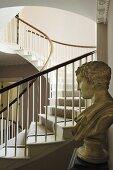 A bust and a curved stairway in the background