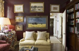 An open door in living room with a light upholstered sofa on a dark red wall