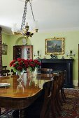 Wooden table and chandelier in front of a fireplace in an elegant dining room with green walls