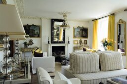 A traditional living room with light upholstered furniture in front of a fireplace and bright yellow curtains at the window