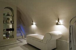 A white lounger in an elegant bathroom with oriental wall lighting, antique jars in a niche and an illuminated flight of stairs