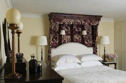 An English bedroom with table and wall lamps, a double bed with a patterned canopy and white bedclothes