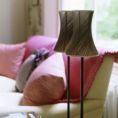 Floor lamps with two lamp shades out of brown fabric and a sofa with pillows