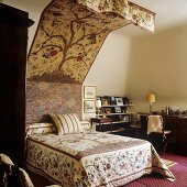 A queen-sized bed and a canopy with the same floral patterned fabric