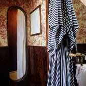 A bathroom with patterned wallpaper and a striped bathrobe hanging next to the open shower cubicle
