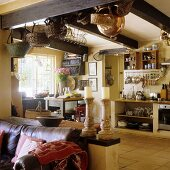 An old leather sofa in front of a room divider and an open-plan kitchen with baskets hanging from the wood beam ceiling