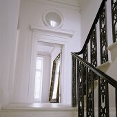 Staircase with black metal bannisters and door opening with a view of a full-length mirror