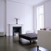 A minimalistic living room with an antique sofa on dark wooden floorboards in front of a fireplace