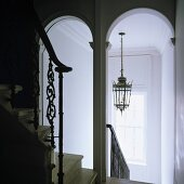 A white-painted stairway with archways and a view of a ceiling lantern