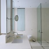 A light-coloured washstand with a mirrored cabinet and a glass partition wall