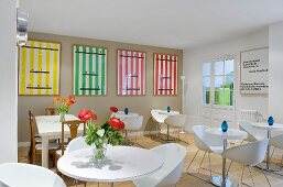 Bar tables and white bucket chairs in a hotel breakfast room with colourful posters on the grey wall