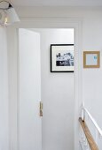An open hotel room door with a view of a picture on the wall