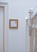 A framed door number on a door in a stairway
