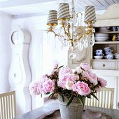 A dining table with a bunch of peonies in a 19th century German thatched-roof house decorated in a Scandinavian style