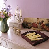 Candles, flowers and a picture on a sideboard
