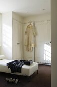 A built-in wardrobe in a dressing room with clothing on a white leather lounger