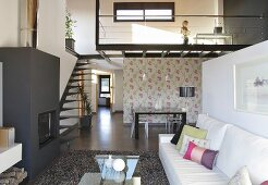 A designer maisonette apartment - a fireplace in living room and a flight of stairs leading to a gallery