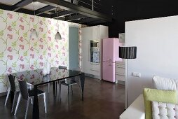 A living-room-cum-dining-room with a black shiny table against a wall hung with floral wall paper and a view into an open-plan kitchen