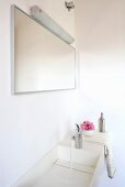 A corner of a bathroom - water running into white wash basin and a mirror with wall lighting