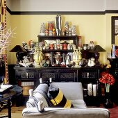 A large collection of vases on a black sideboard against a yellow wall