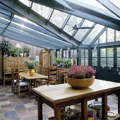 A rustic kitchen table and dining area in a conservatory with a grey steel structure