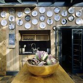 A collection of plates hanging on the wood panelling in a kitchen