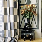 Roses in a black shiny vase on an Oriental box next to a checked curtain