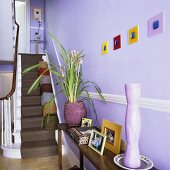 A wall table at the foot of a flight of carpeted stairs in a lilac hallway