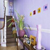 Wandtisch und Treppe mit Läufer im fliederfarbenen Treppenhaus