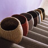 Various coloured sisal baskets on a flight of stairs with a carpet runner
