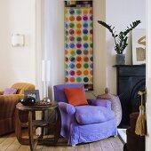 Holzbeistelltisch und violetter Polstersessel vor Kaminwand