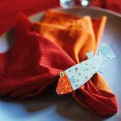 Tellerdeko - Fischfigur auf orangefarbener Stoffserviette
