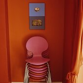 Farbige Stühle gestapelt vor orangefarbener Wand