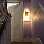 Treppenhaus im Altbau mit Wandleuchte neben offenstehender Zimmertür