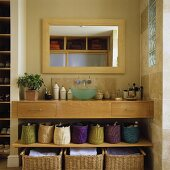 A light wood washstand built into a wall niche with baskets on the shelf below and a mirror above