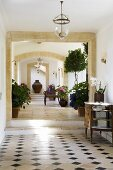 A hallway in a Mediterranean country house with stone archways and a patterned tiled floor