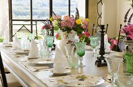 Place settings with wine glasses and vases of flowers