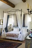 A bedroom in a country house with a metal four poster bed and light curtains