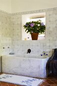 A stone bathtub against a tiled wall with a window and a pot of flowers on the window sill